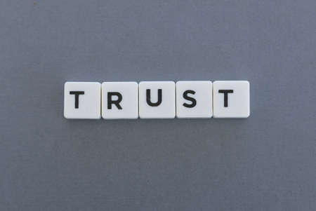 Trust word made of square letter word on grey background.