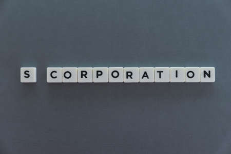 S Corporation word made of square letter word on grey background.