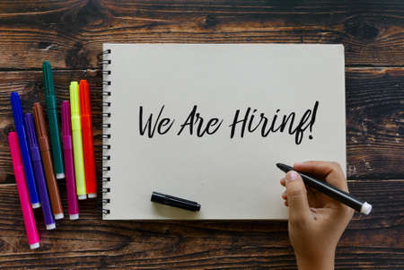 Top view of colorful pen with hand writing  We Are Hiring!  on a notebook on wooden background.