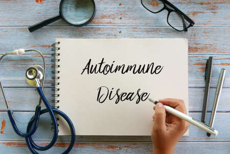 Top view of magnifying glass,glasses,stethoscope,pen and hand writing  Autoimmune Disease  on notebook on wooden background,