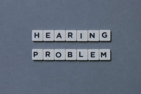 ' Hearing Problem ' word made of square letter word on grey background. Foto de archivo