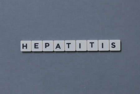 ' Hepatitis ' word made of square letter word on grey background.