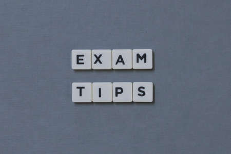 Exam Tips  word made of square letter word on grey background.