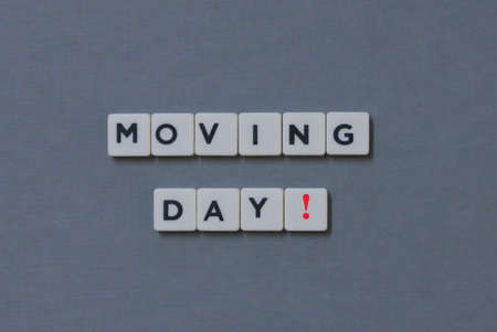 Moving Day!  word made of square letter word on grey background. Imagens