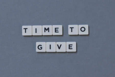 Time To Give  word made of square letter word on grey background.