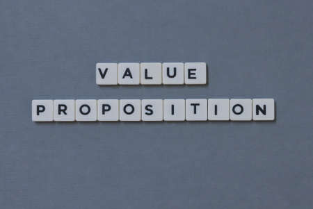 Value Proposition  word made of square letter word on grey background.