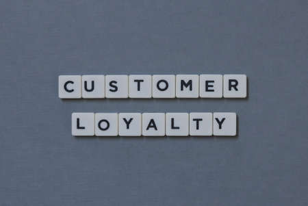 Customer Loyalty  word made of square letter word on grey background.