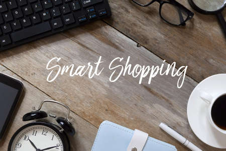 Top view of keyboard,glasses,magnifying glass,coffee,pen,notebook,clock, and smartphone on wooden background written with Smart Shopping. Imagens