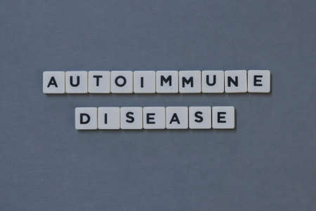 Autoimmune Disease  word made of square letter word on grey background.