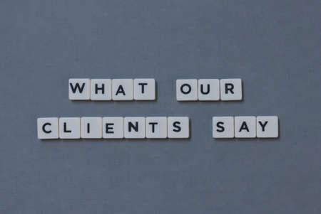 What Our Clients Say  word made of square letter word on grey background. Imagens