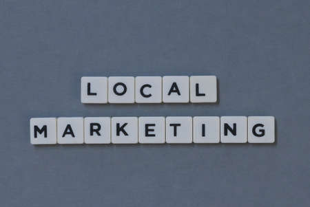 ' Local Marketing ' word made of square letter word on grey background.