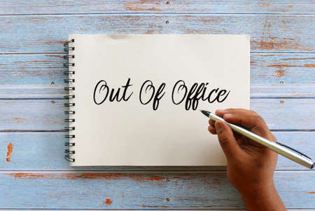Top view of hand holding pen writing Out Of Office on notebook on wooden background. Imagens