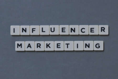 Influencer Marketing  word made of square letter word on grey background. Imagens