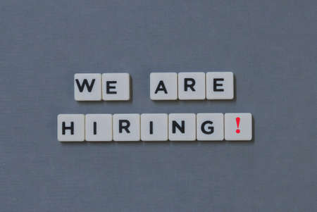 We Are Hiring!  word made of square letter word on grey background. Imagens