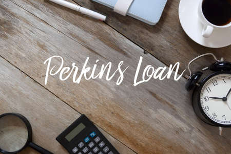 Top view of pen,notebook,coffee,clock,calculator and magnifying glass on wooden background written with Perkins Loan. Imagens