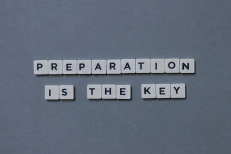 ' Preparation Is The Key ' word made of square letter word on grey background.