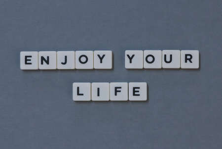 Enjoy Your Life  word made of square letter word on grey background.