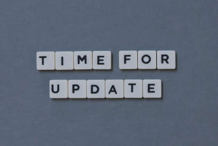 Time For Update  word made of square letter word on grey background. Imagens