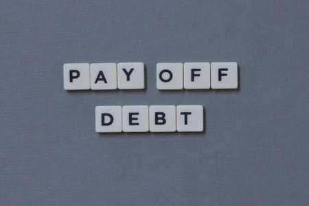 Pay Off Debt  word made of square letter word on grey background.