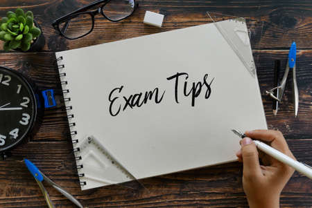 Top view of stationery,clock,glasses,plant and hand holding pen writing Exam Tips on notebook on wooden background.
