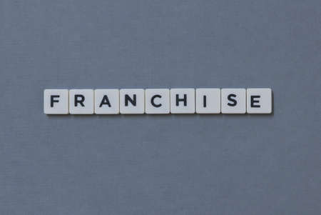 Franchise  word made of square letter word on grey background.