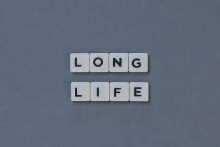 Long Life  word made of square letter word on grey background.