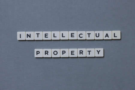 Intellectual Property  word made of square letter word on grey background. Imagens