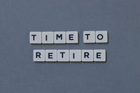 Time To Retire  word made of square letter word on grey background.