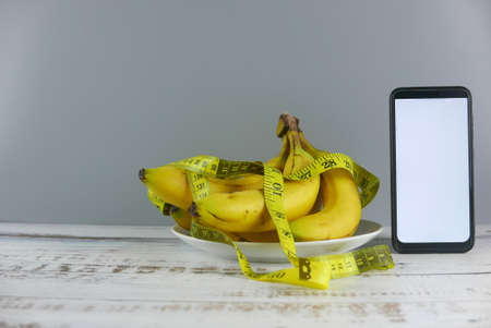 Bunch of bananas,measuring tape and smartphone on wooden background. Mockup for healthy eating, diet, mobile phone application, service, and website. Copy space for text or logo.