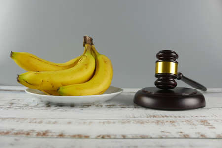 Gavel and bunch of bananas on wooden background. Lawsuit concept.