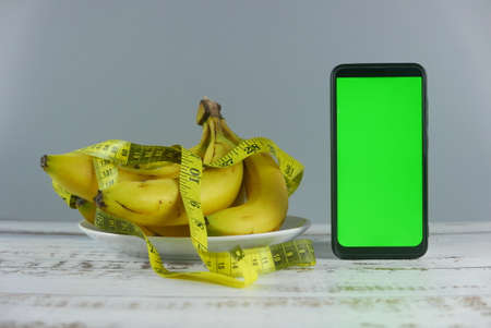 Bunch of bananas,measuring tape and smartphone on wooden background. Mockup for healthy eating, diet, mobile phone application, service, and website.