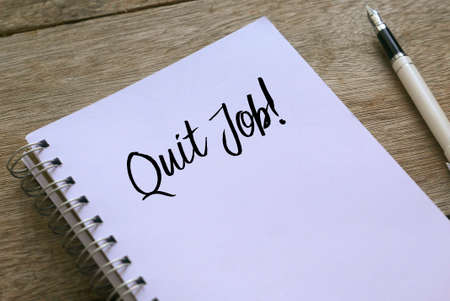 Pen and notebook written with Quit Job! on wooden background.