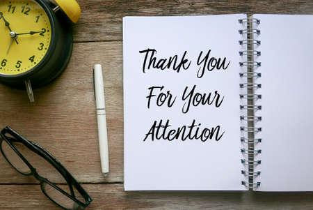 Widok z góry na zegar, okulary, długopis i notatnik napisany z dziękuję za uwagę na drewnianym tle.