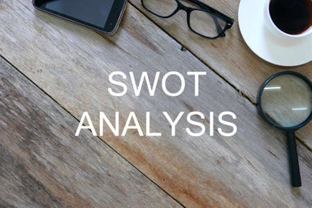 Top view of mobile phone,glasses, a cup of coffee, magnifying glass on wooden background written with SWOT Analysis.