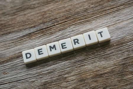 Demerit in alphabet on wooden background.