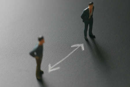 Selective focus of miniature people on a chalkboard with white arrow represent social distance of coronavirus or covid-19 issue. Social distancing concept.