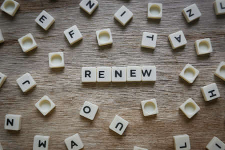Renew word made of square letter word on wooden background.