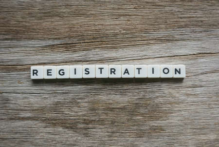 Registration word made of square letter word on wooden background.