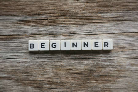Beginner word made of square letter word on wooden background. Stok Fotoğraf