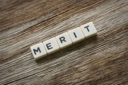 Merit word made of square letter word on wooden background.