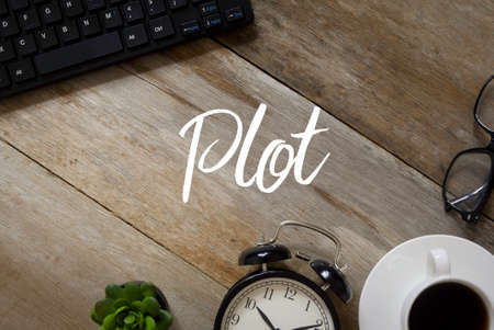Top view of a keyboard,plant,table clock,a cup of coffee and glasses on a wooden background written with Plot.
