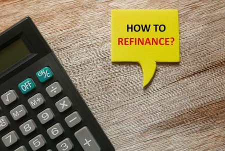 Top view of calculator, and yellow speech bubbles written with question of How to Refinance? on wooden background.