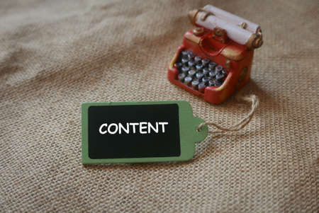 A red miniature of vintage typewriter with wooden tag written with CONTENT.