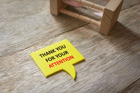 Sand clock with a yellow speech bubble written with Thank You For Your Attention on wooden background.