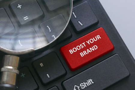Magnifying glass on a computer keyboard with red button written with advice Boost your brand. Foto de archivo
