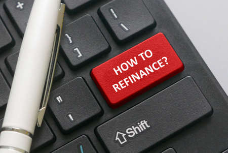 Selective focus of a pen and keyboard with red button written with question of How to refinance?. Business and finance concept.