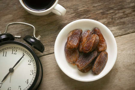 Selective focus and top view of a dried dates fruit in a white bowl together with a cup of coffee and vintage clock on wooden background. Ramadan holy month for muslim concept where they are fasting.
