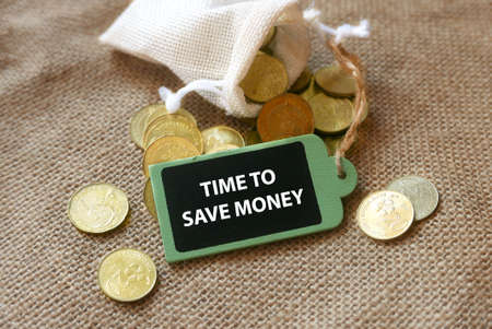 Selective focus of gold coins and wooden tag written with advice ' Time to save money ' on rugs background.