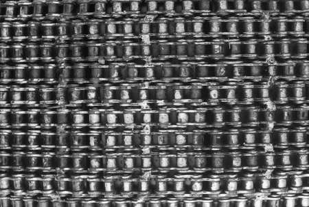 A stack of stainless steel motorcycles chain in a black and white. Use as a background