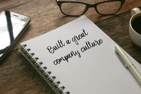 Selective focus of mobile phone,glasses,a cup of coffee,pen and notebook written with ' Built a great company culture ' on wooden background.